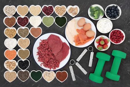 maca: Body building equipment and health food with meat, fish, supplement powders, dairy, fruit, vegetables, pulses, nuts, seeds, grains and cereals on porcelain plates. Stock Photo