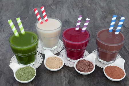 Health food supplement drinks of wheat grass, maca herb root, acai berry and chocolate whey with corresponding supplement powders in bowls. Also used by body builders. Stock Photo