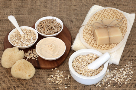 Natural oat skincare treatment and cleansing products on hessian background.