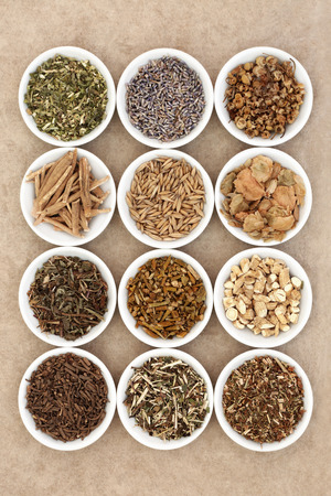homoeopathic: Sleeping and calming herb selection in white china dishes on natural hemp paper background.