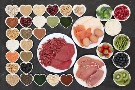 Body building health food with meat, fish, supplement powders, dairy, fruit, vegetables, pulses, nuts, seeds, grains and cereals on porcelain plates. Stock Photo