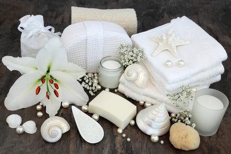 Flor de lirio blanco con accesorios de belleza para el tratamiento de la belleza incluyendo loofah natural, crema hidratante, jabón, franelas, sal, esponja natural con conchas y perlas.