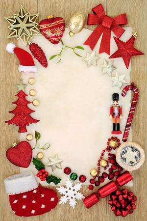 Christmas background border with bauble decorations, mince pie, foil wrapped chocolates, holly and  mistletoe on parchment paper oak wood.