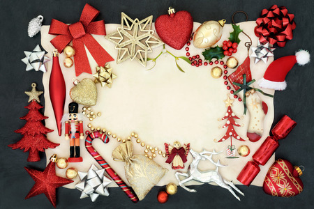 Christmas background border with bauble decorations, holly, mistletoe and ornaments on parchment paper on slate. Stock Photo - 83420039