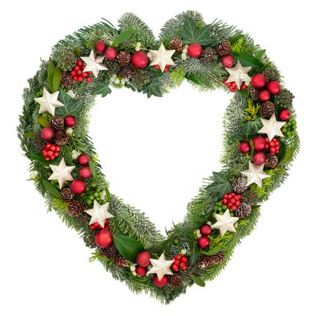 Hartvormige kerstkrans met sterren- en snuisterijen, holly, maretak, klimop, dennenbomen, sneeuw bedekte blauwe spar en jeneverbes op witte achtergrond. Stockfoto