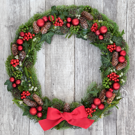 Traditional christmas wreath with red bow, bauble decorations, holly, mistletoe, ivy, snow covered winter greenery on distressed white wood background. Stock Photo
