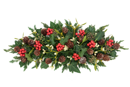 Centrepiece: Christmas and winter decoration with holly, ivy, mistletoe, fir and pine cones on white background. Stock Photo