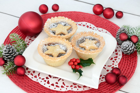 Homemade christmas mince pies on a plate with holly, fir and  red bauble decorations on a place mat on distressed white wood background.