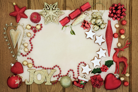 Christmas background border with gold joy sign, gingerbread biscuits, bauble decorations, holly, mistletoe and foil wrapped chocolates  on parchment and oak wood.