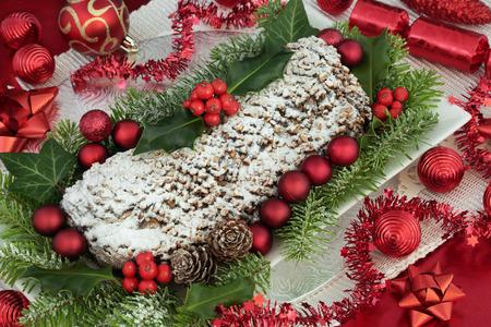 De stuifmeelcake van Kerstmischocolade op een plaat met hulst, spar en klimop en rode snuisterijdecoratie.