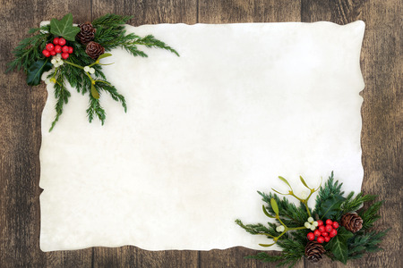 Old fashioned christmas background border with holly, mistletoe, ivy, juniper fir and pine cones on parchment paper over rustic old oak wood. Stock Photo