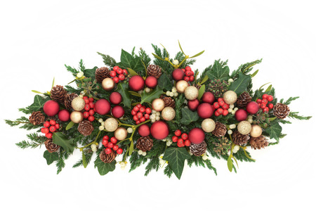 Christmas centrepiece decoration with red and gold bauble decorations, holly, ivy, mistletoe, fir and pine cones on white background. Stock Photo