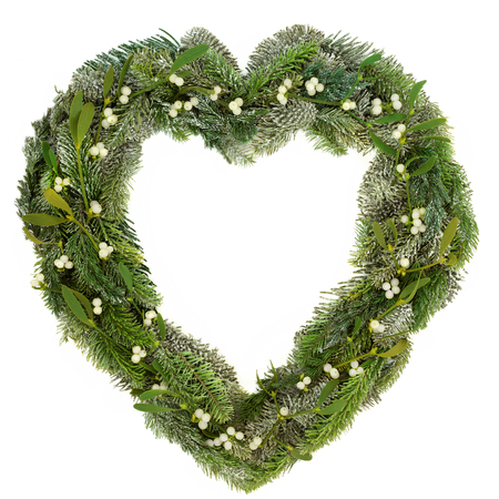 Heart shaped wreath with mistletoe, snow covered blue spruce and juniper fir on white background.