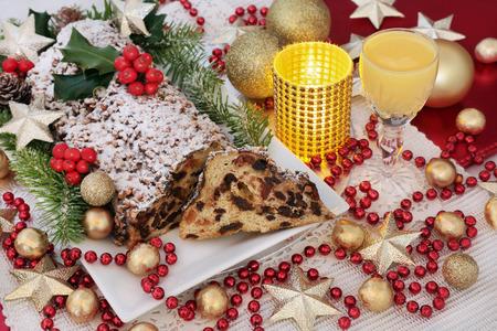 Kerst chocolade stol cake op een bord met eieren nog, hulst, spar en klimop en goud bauble en rode kraal decoraties.
