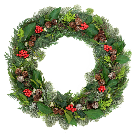 Christmas and winter wreath decoration with holly, mistletoe, juniper fir, blue spruce, cedar, pine cones and ivy leaves on white background. Stock Photo - 86447216