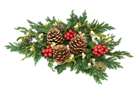 Christmas floral decoration with holly, gold pine cones, mistletoe, cedar cypress and juniper leaf sprigs and ivy on white background. Foto de archivo