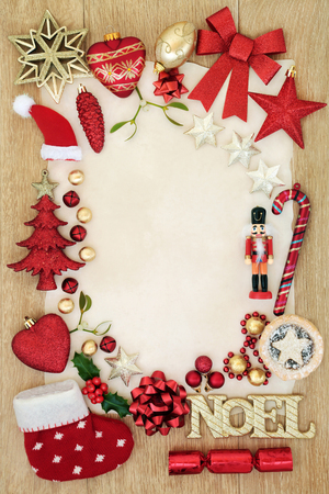 Christmas background border with bauble decorations, gold noel sign, mince pie, foil wrapped chocolates, holly and  mistletoe on parchment paper oak wood.