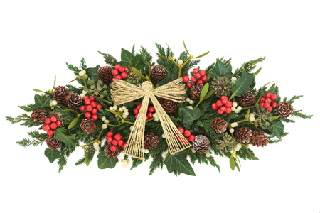 Christmas decoration with gold metal bow, holly, ivy, mistletoe, fir and pine cones on white background. Stock Photo