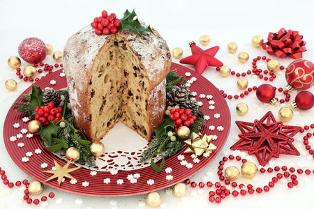 Chocolate panettone christmas cake with bauble decorations, foil wrapped chocolates, small snowflakes, hiolly and winter greenery on white glitter background.