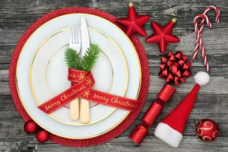Christmas table place setting with dinner plates, napkin, cutlery, fir, ribbon, santa hat, candy canes, cracker and bauble decorations on rustic wood background.