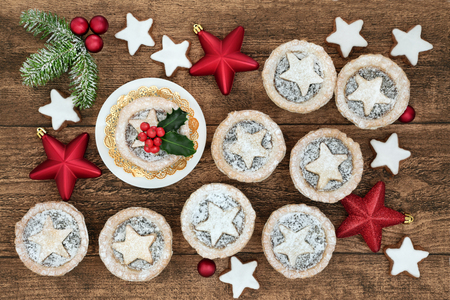 Christmas mince pie tarts with gingerbread star biscuits, red bauble decorations, holly and fir on oak background.
