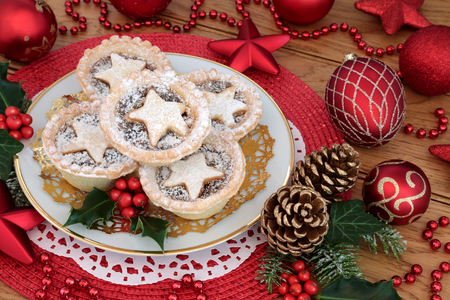 Christmas star miince pies with icing sugar dusting on a plate with bauble decorations, holly, ivy, pine cones and fir on oak wood background.