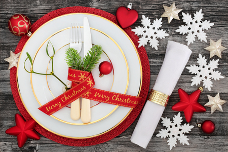 napkin ring: Merry christmas ribbon and table place setting with plates, napkin, cutlery and fir with bauble decorations on red mat on rustic wood background.