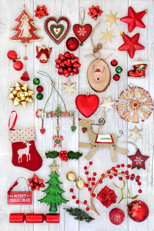 Christmas decorations with old fashioned and new baubles, holly, mistletoe and fir on rustic  white wood background.