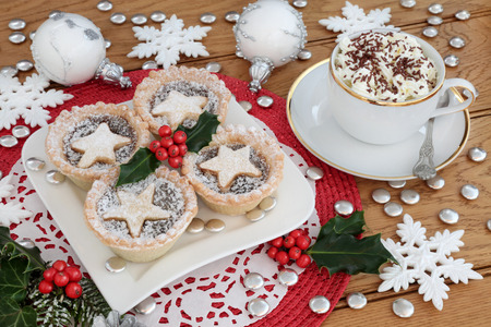 Christmas mince pies on a plate with hot chocolate drink, holly and bauble decorations on a white dolie on a red place mat on oak background. Stok Fotoğraf