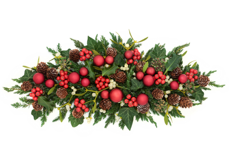 Christmas decoration with red bauble decorations, holly, ivy, mistletoe, fir and pine cones on white background.