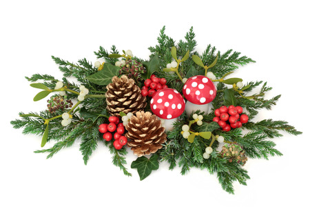 Christmas decoration with fly agaric mushroom ornaments, holly, pine cones, mistletoe, cedar cypress and juniper leaf sprigs and ivy on white background. Stock Photo