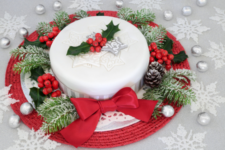 Festive iced christmas cake with red bow, holly, fir, snowflake and bauble decorations with silver foil wrapped chocolates on glitter background. Stock Photo
