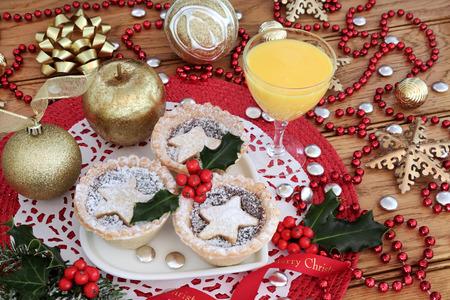Kerst gehakt pasteitjes taarten met hulst op een hartvormige plaat met ei nog, goud bauble decoraties en rode kraal streng op eiken tafel achtergrond ..