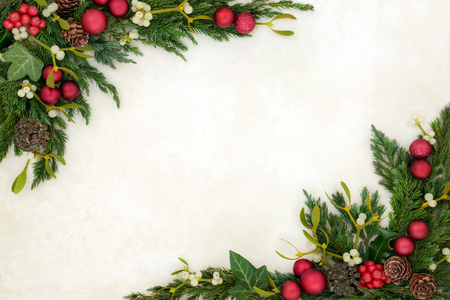 Christmas decorative background border on parchment paper with red bauble decorations, holly, mistletoe, ivy, fir and pine cones.