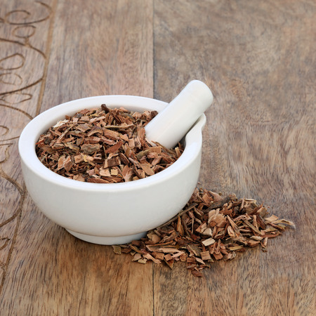 White willow bark herb used in alternative herbal medicine and has pain relieving and anti inflammatory properties and is similar to aspirin in its effects, in a mortar with pestle on rustic wood background. Salix alba.