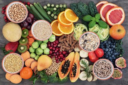 Concepto de alimentos saludables para una dieta alta en fibra con frutas, verduras, cereales, pasta integral, granos, legumbres y hierbas. Alimentos con alto contenido de antocianinas, antioxidantes, carbohidratos inteligentes y vitaminas en la vista superior de fondo de mármol.