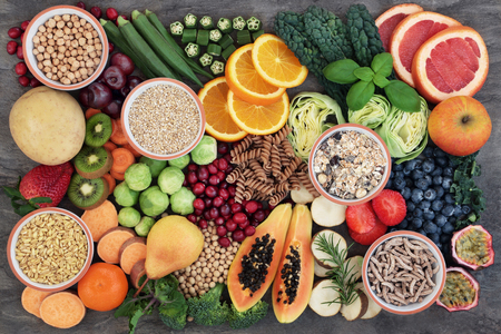 Health food concept for a high fiber diet with fruit, vegetables, cereals, whole wheat pasta, grains, legumes and herbs. Foods high in anthocyanins, antioxidants, smart carbohydrates and vitamins on marble background top view. Stock Photo