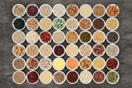 Macrobiotic health food with a large selection of legumes, seeds, nuts, grains, vegetables, cereals and whole wheat pasta with super foods high in protein, omega 3, anthocyanins, antioxidants, minerals and vitamins on marble background, top view. Stock Photo