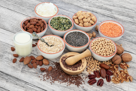 Vegan health food with soya beans, seeds, nuts, soya milk, yoghurt and chunks. Foods high in fiber, antioxidants, vitamins and minerals.  On rustic wood background. Stock fotó