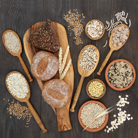 High fiber health food concept with fresh whole grain bread rolls, cereals and grains. Rustic background on oak, top view.