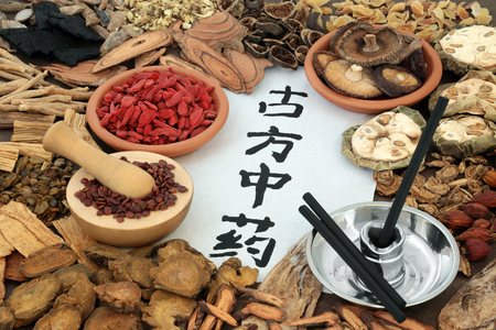 Herbs used in chinese herbal medicine with moxa sticks used in alternative moxibustion therapy. Calligraphy script translates as traditional ancient chinese medicine. Stock Photo