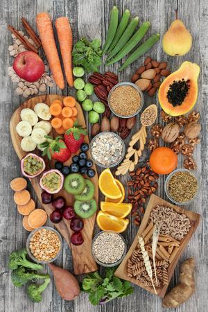 Concept d'aliments santé pour une alimentation riche en fibres avec fruits, légumes, céréales, noix, graines, pâtes de blé entier, céréales, légumineuses et épices. Aliments riches en oméga 3, anthocyanes, antioxydants et vitamines sur la vue de dessus de fond rustique.