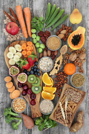 Health food concept for a high fiber diet with fruit, vegetables, cereals, nuts, seeds, whole wheat pasta, grains, legumes and spice. Foods high in omega 3, anthocyanins, antioxidants and vitamins on rustic background top view.