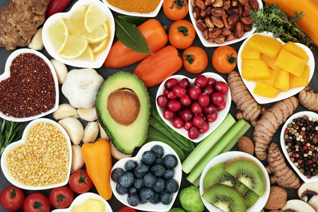 Health food for fitness concept with fresh fruit, vegetables, pulses, herbs, spices, nuts, grains and pulses. High in anthocyanins, antioxidants, smart carbohydrates, omega 3 fatty acids,  minerals and vitamins.
