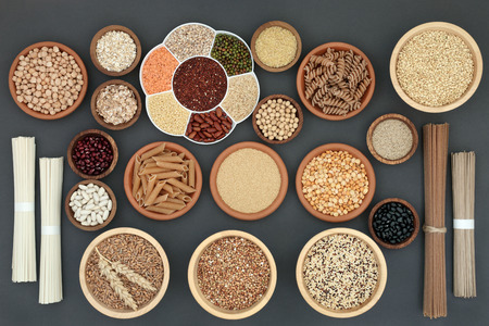 Healthy dried macrobiotic food with soba and udon noodles, pulses, cereals, whole wheat pasta, seeds and cereals with foods high in protein, omega 3, anthocyanins, antioxidants, minerals and vitamins on rustic background, top view.