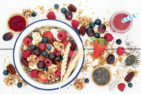Macrobiotic health food for breakfast concept with acai berry smoothie and powder, granola, pollen grain,  berry fruit, chia seed and nuts with foods high in protein, omega 3, anthocyanins, antioxidants, minerals and vitamins on rustic background, top view.