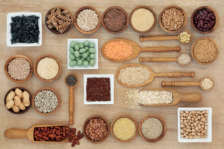 Dried macrobiotic diet health food concept with legumes, seaweed, grain, cereal, nuts, seeds and whole wheat pasta. High in smart carbohydrates, protein, antioxidants and fibre,  top view.