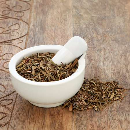 Yerba mate santa herb used in alternative herbal medicine to treat coughs, colds, asthma and bronchitis in a mortar with pestle on rustic wood background. Eriodictyon californicum.