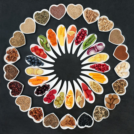 Health food wheel for a healthy heart concept with vegetables, fruit, fish, nuts, seeds, supplement powders, cereal and herbs for herbal medicine. High in omega 3 fatty acid, anthocyanins, fiber, antioxidants and vitamins.