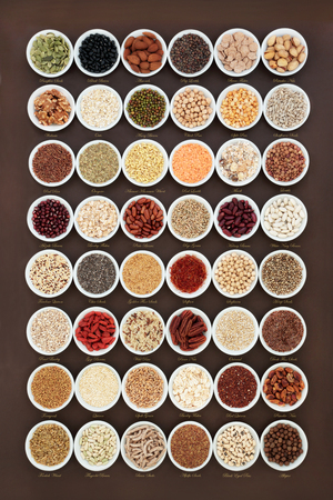 High fiber health food sampler with cereals, nuts, seeds, grain, fruit, herbs and legumes with foods high in omega 3 fatty acid, antioxidants and vitamins, top view. With titles.